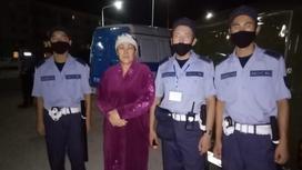 Женщина стоит вместе с военнослужащими Нацгвардии Казахстана