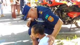 Спасатель держит за спину ребенка