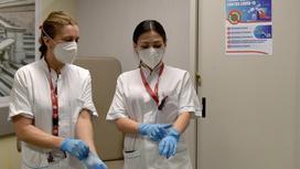 Две медсестры надевают перчатки