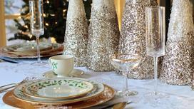 Красиво украшенный новогодний стол с тарелками и бокалами
