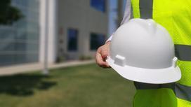строитель держит в руках защитную каску