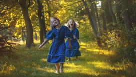 Девочки-близняшки бегут в синих платьях по роще