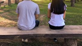 Парень и девушка сидят на скамейке