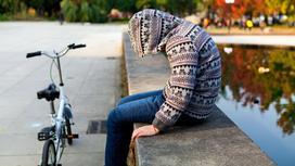 Мальчик сидит у фонтана с велосипедом