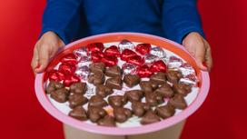 Женщина держит поднос с конфетами