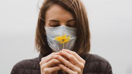Женщина в маске держит цветок