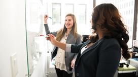 Офисные сотрудницы пишут маркерами на доске