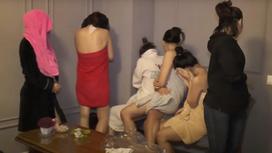 Девушки стоят, отвернувшись от камеры