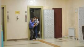 Охранник пытается схватить журналистку, чтобы вытащить ее из здания акимата в Алматы