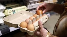 Женщина открывает упаковку с яйцами