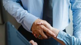 Мужчина в рубашке жмет руку женщине