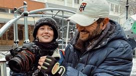 Анастасия Ивлеева стоит рядом с мужчиной с камерой
