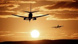 Два самолета летят на фоне заката