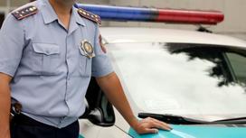 Полицейский облокотился на капот машины