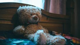 Игрушечный медведь сидит на кровати