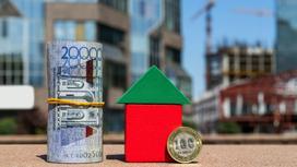 Свернутая купюра 20 тысяч тенге и монета 100 тенге стоят рядом с кубиками в виде дома