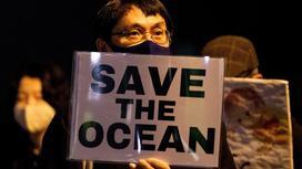"""Мужчина держит в руках плакат с надписью """"Спасем океан"""""""""""