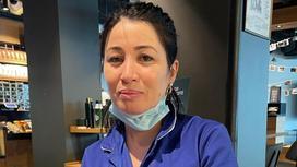 Женщина в синей одежде с медицинской маской