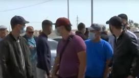 Мужчины в масках стоят на улице в Актау