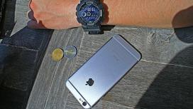 Мужчина положил смартфон на стол рядом с монетами