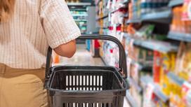 Девушка стоит с продуктовой корзиной рядом с полкой в супермаркете