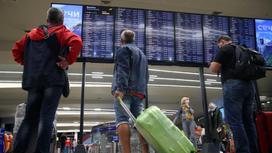 Авиапассажиры с багажом смотрят на табло
