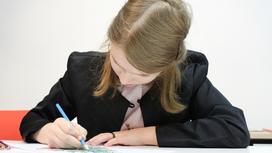 школьница пишет в тетрадке