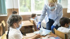 Учитель наносит антисептик на руки ученице