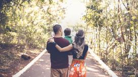 Семья с ребенком идет по дороге