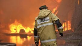 Пожарный стоит на фоне горящего здания