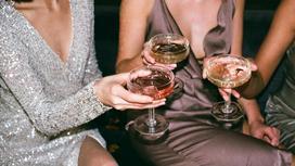 Девушки поднимают руками бокалы со спиртным