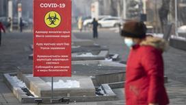 Женщина в красной куртке и маске идет по улице