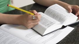 Девушка сидит за столом с книгой и рабочей тетрадью