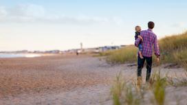 Мужчина с ребенком гуляют по пляжу