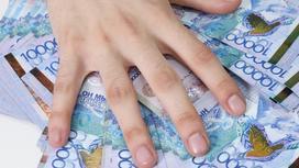 рука мужчины лежит на купюрах тенге