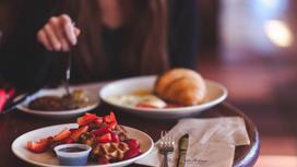 Девушка обедает за столом в кафе