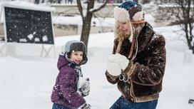 Мама и сын играют в снежки