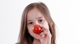 Девочка держит помидор около носа