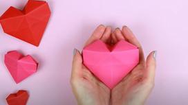 В руках держат розовое бумажное сердце, рядом лежат на столе еще три бумажных сердца