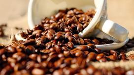 Зерна кофе, высыпавшиеся из чашки