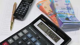 калькулятор лежит на столе рядом с пачкой денег