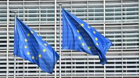 Флаги Евросоюза развиваются на фоне здания ЕС в Брюсселе
