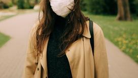 Девушка в маске стоит на улице