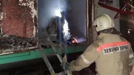 Сотрудник пожарной охраны у сгоревшего вагона поезда