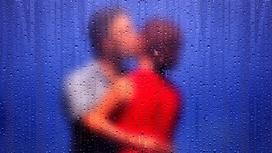 Женщина и мужчина целуются за пеленой дождя