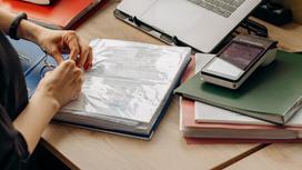Женщина берет документы из папки