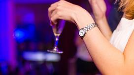 девушка держит в руке бокал с напитком