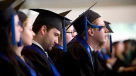 Студенты-выпускники сидят в мантиях