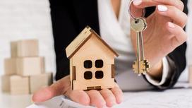 Женщина держит ключи и игрушечный дом