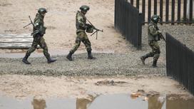 Военные идут с оружием в руках